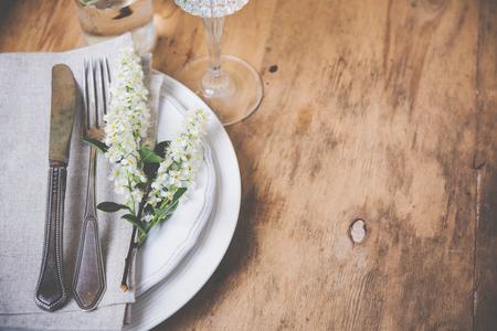 Vintage table de style décoration avec des fleurs de cerisier et oiseau vieux couverts, festif décor de table rustique