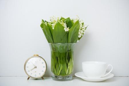 arreglo floral: la decoración del hogar simple, lirios del valle en un florero en el estante de la pared de fondo blanco