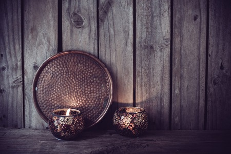 cobre: Burning candles and a copper tray on an old wooden board background, vintage decor