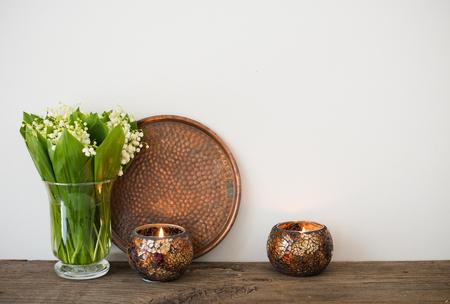 cobre: la decoración del hogar simple, lirios del valle en un florero y velas en el estante de la pared de fondo blanco