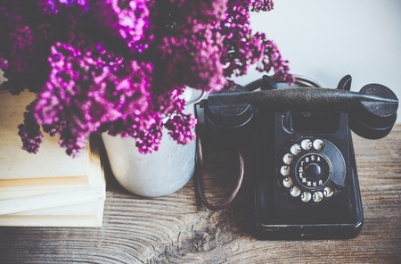 the white house: Home interior decor, bouquet of lilacs in a vase, a vintage rotary phone and books on rustic wooden table, on a white wall background