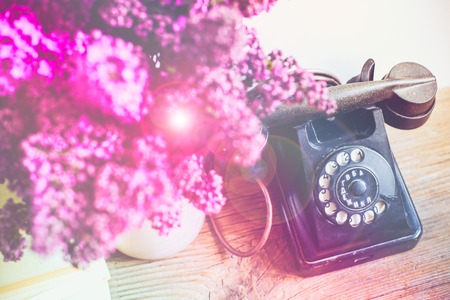 wall decor: Home interior decor, bouquet of lilacs in a vase, a vintage rotary phone and books on rustic wooden table, on a white wall background
