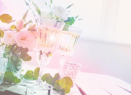 Twee glazen champagne en witte bloemen, kaarsen op een oude vintage rustieke houten tafel. Vintage zomer bruiloft tafeldecoratie. Feestelijk decor.