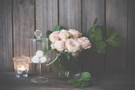 arreglo floral: decoración de la mesa de boda elegante de la vendimia con las rosas y velas cerca de la pared de la tabla de madera vieja Foto de archivo