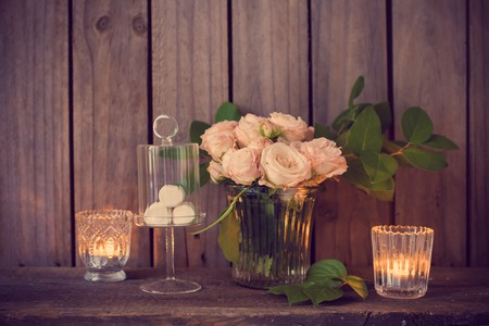 burning: Elegant vintage wedding table decoration with roses and candles near the wall of old wooden board