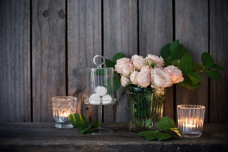 Elegant vintage wedding table decoration with roses and candles near the wall of old wooden board