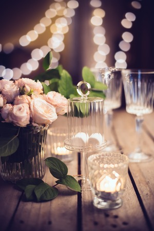 Elegant vintage wedding table decoration with roses and candles, warm night light filter