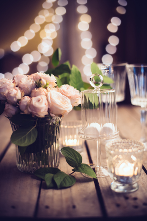 candle light table setting: Elegant vintage wedding table decoration with roses and candles, warm night light filter