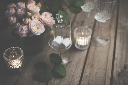 table setting: Elegant vintage wedding table decoration with roses and candles, warm night light filter