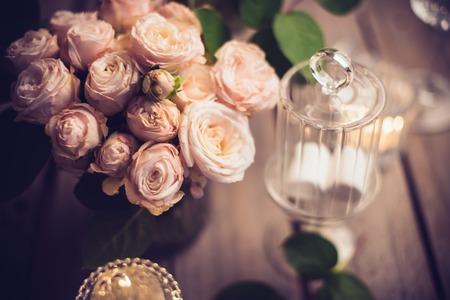 Elegant vintage bröllopsbord dekoration med rosor och ljus, varmt nattljus filter Stockfoto