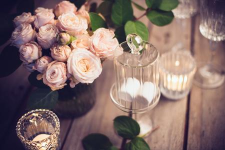 Elegant vintage bruiloft tafeldecoratie met rozen en kaarsen, warme avond licht filter