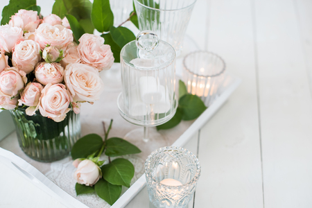 white wedding: Beautiful vintage wedding table decorations with roses, candles, cutlery and  sweets in a jar. Stock Photo