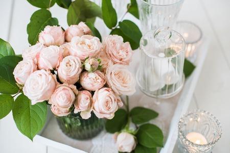 Mooie vintage bruiloft tafeldecoratie met rozen, kaarsen, bestek en snoepjes in een pot.