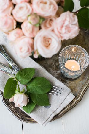 rosas blancas: decoraciones de época hermosa mesa de boda con rosas, velas, cubiertos y dulces en un frasco. Foto de archivo
