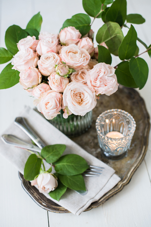 white rose: Beautiful vintage wedding table decorations with roses, candles, cutlery and  sweets in a jar. Stock Photo