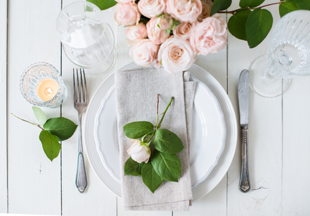 arrangements: Beautiful vintage wedding table decorations with roses, candles, cutlery and  sweets in a jar. Stock Photo