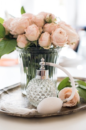 feminine background: Elegant composition in retro style, vintage perfume bottle and a bouquet of roses on a silver tray on ladies dressing table