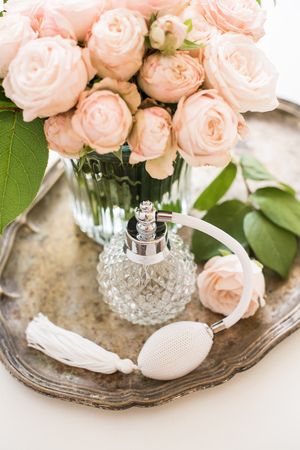 table decoration: Elegant composition in retro style, vintage perfume bottle and a bouquet of roses on a silver tray on ladies dressing table