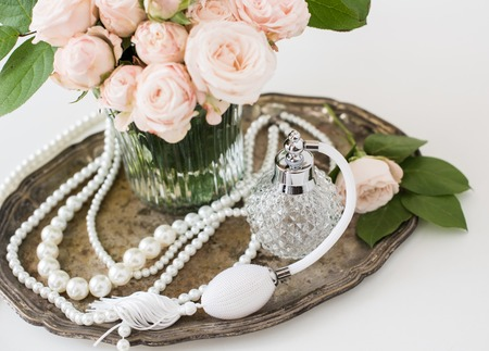 Elegant composition in retro style, vintage perfume bottle and a bouquet of roses on a silver tray on ladies dressing table