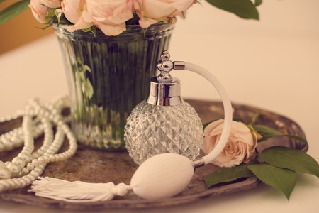 perfume spray: Elegant composition in retro style, vintage perfume bottle and a bouquet of roses on a silver tray on ladies dressing table