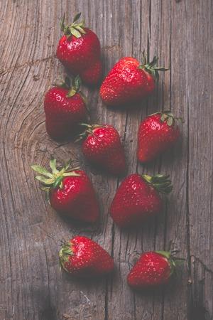 frescura: fresas orgánicas rojos maduros en un viejo fondo de madera bordo rústico Foto de archivo