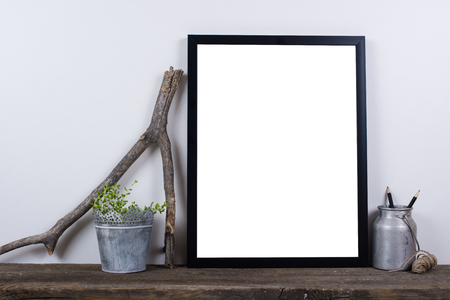 Scandinavian style empty photo poster frame mock up. Minimal home decor on rustic wooden board with white wall background.