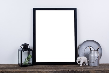 pictures: Scandinavian style empty photo poster frame mock up. Minimal home decor on rustic wooden board with white wall background.