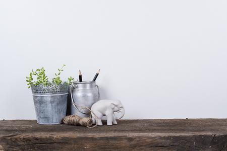 植物と素朴な木の板と白い壁の背景のスカンジナビア様式の家の装飾。