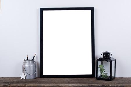 北欧スタイルの空写真ポスター フレーム モックアップ。白い壁の背景を持つ素朴な木の板に最小限の家の装飾。