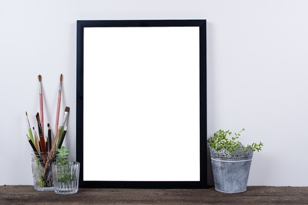 wall decor: Scandinavian style empty photo poster frame mock up. Minimal home decor on rustic wooden board with white wall background.