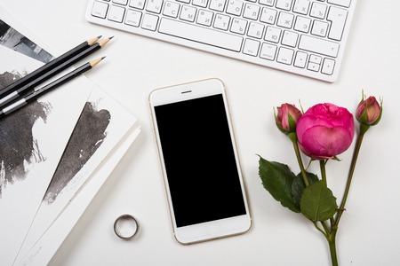 blogger: Modern smartphone, computer keyboard and fesh pink flowers on white table, freelancer blogger workspace, screen mockup