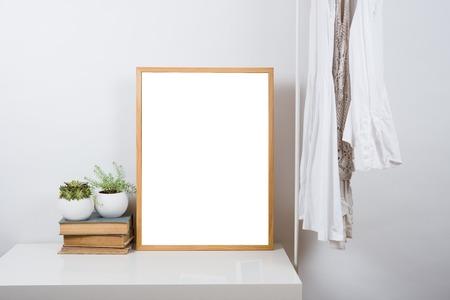 El marco vacío de madera sobre la mesa en la sala blanca interior, el arte de diseño listo para imprimir maqueta Foto de archivo