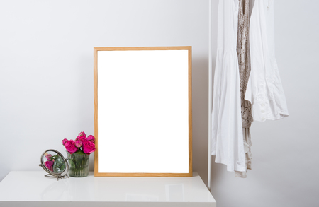 contemporary interior: Empty wooden picture frame on the table in white room interior, art print design ready mock-up Stock Photo