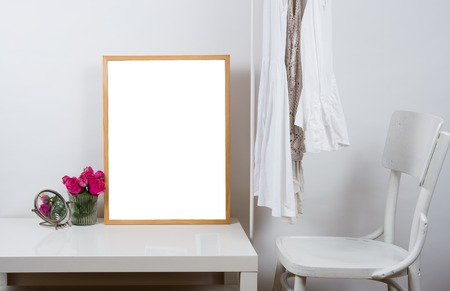Empty wooden picture frame on the table in white room interior, art print design ready mock-up