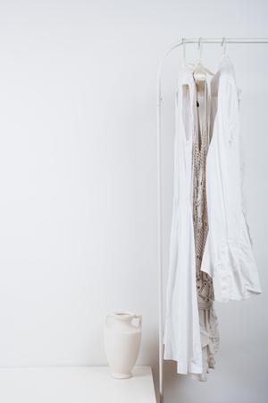 Dame slaapkamer witte interieur, kleding op de hanger op de muur achtergrond met bopyspace