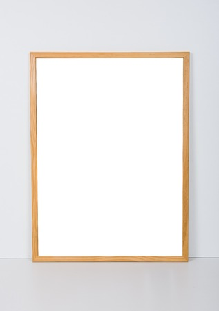 frame wall: Empty wooden frame on the table near the white wall, interior poster mock-up Stock Photo
