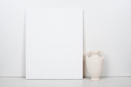 canvas: Empty blank white canvas on a white background, home interior decor, painting poster mock-up