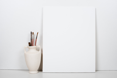Empty blank white canvas on a white background, home interior decor, painting poster mock-up