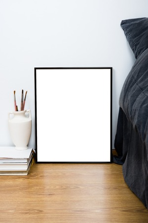bedside: Empty blank classic black frame on a floor, minimal home bedroom interior decor, painting art poster mock-up