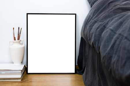 poster bed: Empty blank classic black frame on a floor, minimal home bedroom interior decor, painting art poster mock-up