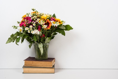 simple: Interior home decor with flowers and books, simple summer decor with copyspace Stock Photo