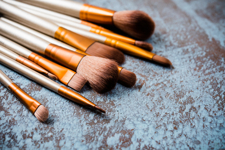 Professional makeup brushes collection, new make-up tools set on painted background with copy space
