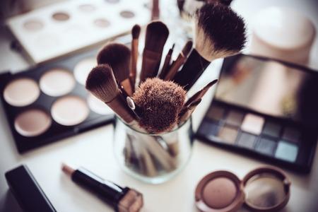 pennelli trucco professionale e strumenti, prodotti make-up set sul tavolo bianco.