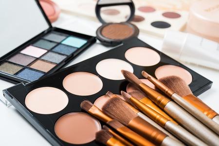 전문 메이크업 브러쉬 및 도구, 천연 메이크업 제품 세트, eyeshadows 및 흰색 테이블에 concealers.
