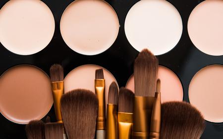 Professionele make-upborstels en hulpmiddelen, natuurlijke geplaatste make-upproducten, oogschaduws en camouflagestiften op witte lijst.