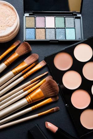 black makeup: Professional makeup brushes and tools collection, make-up products set on black  table background. Stock Photo