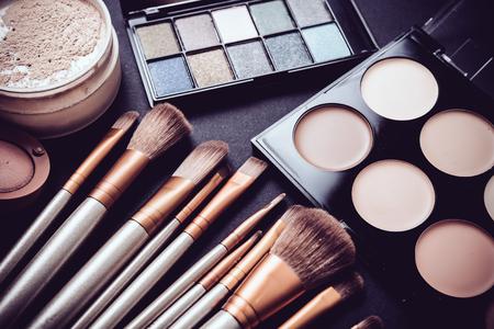 Profesjonalny makijaż pędzle i narzędzia gromadzenia, produkty wymienione na czarnym tle tabeli make-up. Zdjęcie Seryjne