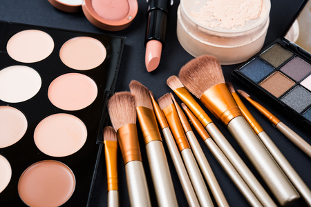 Professional makeup brushes and tools collection, make-up products set on black table background.