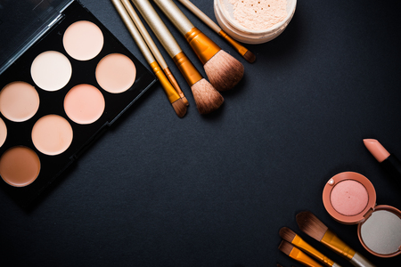 Professional makeup brushes and tools collection, make-up products set on black  table background. Фото со стока