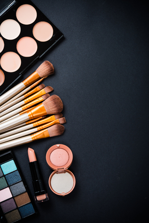 table set: Professional makeup brushes and tools collection, make-up products set on black  table background. Stock Photo
